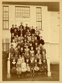 Large group of school children pose on steps of school