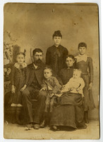 Studio portrait of family with parents seated, children standing and sitting with them