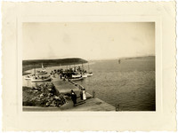 Naknek Cannery - People walking on small pier with several small sailing vessels docked