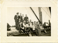 Machinist Crew - A group of men stand and sit in rows on deck of sailing vessel