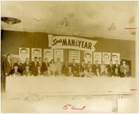 Twenty seven men and one woman pose behind a banquet table under a banner that reads