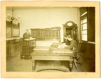 Interior of Whatcom County Treasurer's office with two clerks seated and Treasurer Victor Augustin Roeder at desk on left