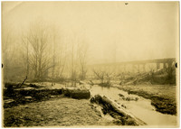 Snow-dusted Whatcom Creek with several fallen logs and a bridge partially visible in the fog