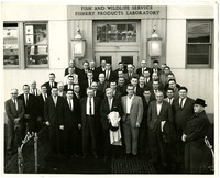 """Forty four men in suits pose outside the doors of """"Fish and Wildlife Service, Fishery Products Laboratory"""" building"""
