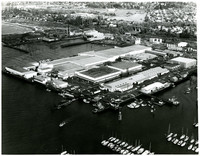 Aerial view of industrual waterfront with massive warehouses standing on landfill pier, surrounded by docks and moored boats, Bellingham, WA.