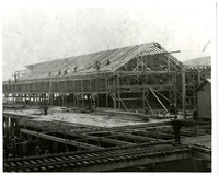 Long, horizontal wood frame building under construction on pier next to railroad tracks