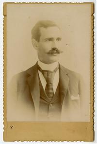 Studio portrait of unidentified mustachioed man in suit and tie