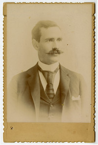 Studio portrait of unidentified mustachioed man in suit and tie