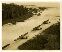 Aerial view of five small, single-propeller pleanes parked on a dirt landing strip with forest on either side and beach beyond
