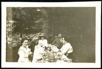 Five people sit at a well-appointed table outdoors in the woods