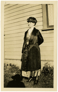 A finely dressed older woman in silk coat poses beside house