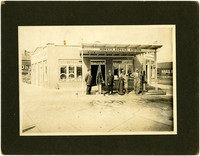 Four men stand next to pumps at Horst's Service Station