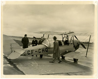"""Four unidentified men standing by a single engine biplane with """"CF-CHQ"""" on its body and top wings."""
