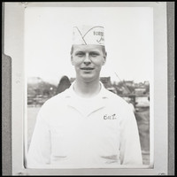 An unidentified young man wearing a white Bornstein Seafoods hat and white shirt with his name (Burl or Burt) sewn above the right pocket