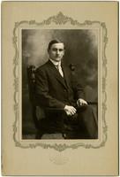Studio portrait of seated man