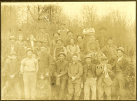Group of about twenty three men and two women and a little girl, most wearing work clothes, posing in forest clearing