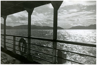 Islands and water viewed through railings from mid-deck of a ship