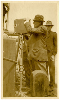 Two men stand on dock covered in marine ropes, one man operating a camera on a tripod