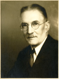 Unidentified man wearing a dark suit and tie, white shirt, round wire-rimmed glasses.