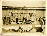 Cast of stage production pose on stage with band seated below stage