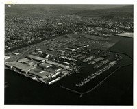 Aerial view of Bellingham, WA, harbor, marina with breakwater, and industrial waterfront, with city in background