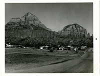 Several ranch-style homes sit at base of two buttes rising above them