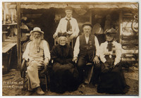 Three elderly men and two elderly women wearing commemorative ribbons in front of log cabin at Old Settlers' Picnic, Whatcom county, WA
