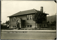 Exterior of two-story, brick Carnegie Library with arched front doorway, Burlington, Washington
