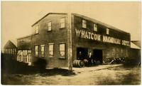 "Thomas Burus Machine Shop - two men pose among wheel rims outside large shop that reads ""Whatcom Machinery Depot"""
