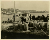 """Tugboat """"Captain"""" tied at dock with barrels and dock workers"""