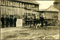 A man and little boy stand with two draught horses hitched to a deliver wagon that reads B.L.&T.Co. in front of a warehouse, with four men in suits standing to the left