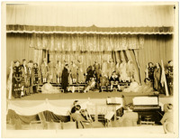 A full cast of actors in costume pose on a stage with several musicians sitting in orchestra pit below