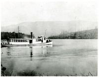 """Several people sit at prow of steam lauch """"Elsinore"""" on Lake Whatcom, WA"""