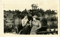 Young man and older woman pose looking at each other near car and picnic table