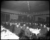 Large dining hall decorated with U.S. flags and over one hundred military men dressed in various army and navy uniforms