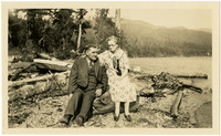 Man and woman sit on log at beach surrounded by forest
