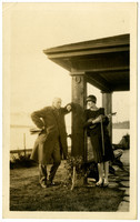 Dapperly dressed man and woman lean against pillar of terrace with Bellingham Bay in background