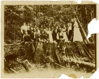 Unidentified men and women with logged tree stump