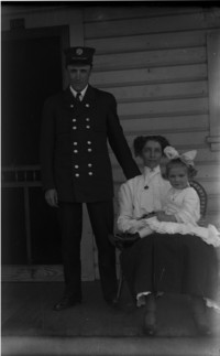Man in uniform standing beside woman in rocking chair holding child on front porch of house