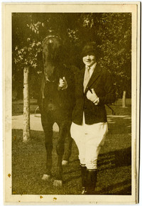 Woman in formal riding costume with jodhpurs and jacket stands next to horse