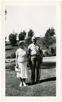 Man and woman pose in park-like landscaping