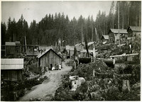 Mining camp  on deforested hillside with family posed next to building in center