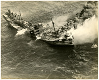 Aerial view of sinking ship with smoke billowing from hull