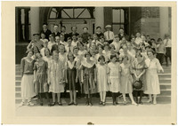School children stand in several rows on steps of school