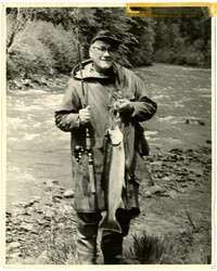Unidentified fisherman holding rod and large fish with rushing river in background