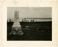 Burial monument overlooking plain with water of Puget Sound in distance