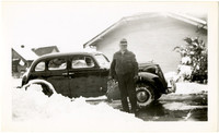 Man stands next to car on snow-shoveled driveway next to houses and yards covered in snow