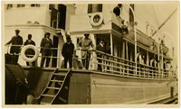 Men in suits stand at rail of deck of S.S. Norwood