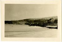 Train progresses on trestle over snowy lake