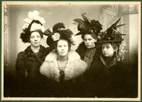 Studio portrait of four young women dressed in fancy hats and fur-trimmed coats